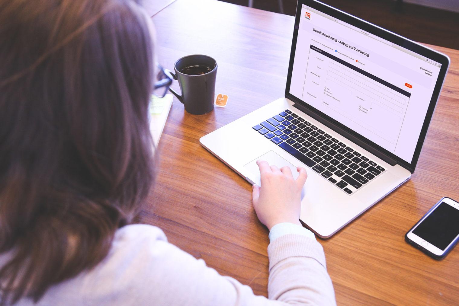 Nutzerin bearbeitet Online-Formular am Laptop
