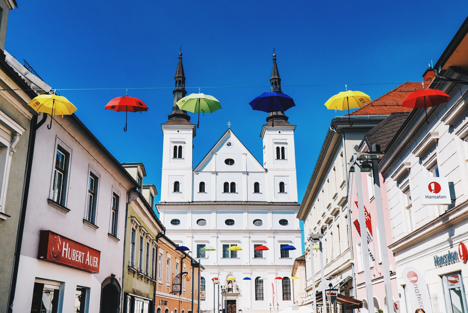 Regenschirme in der Timmersdorfergasse mit Stadtpfarrkirche im Hintergrund